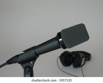 Microphone with headphones in background