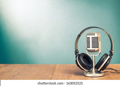 Microphone and headphones on table in front aquamarine wall background