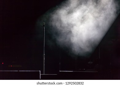 Microphone holder standing on a black dark scene, smoke illuminated by white spotlight at the side, below are stage monitors. Microphone stand on stage.