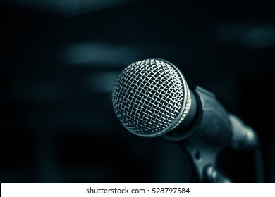 Microphone with metal body in holder on blur background. Close-up, selected focus