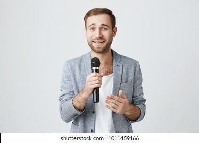 Microphone, music, songs, leisure time concept. Good-looking caucasian male singer looks at camera happily, holds microphone in his hand, smiles broadly. Positive bearded man singing