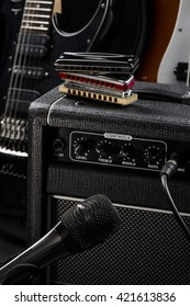 Microphone is near musical instruments such as electric and bass guitars and harmonicas.