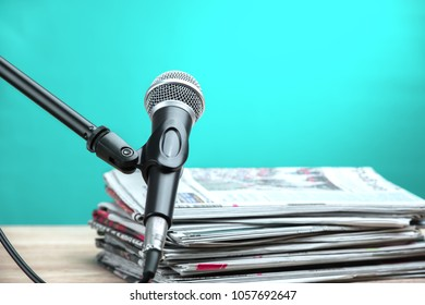 Microphone with newspaper on wooden table - announcement concept