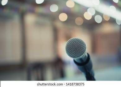 Microphone on abstract blurred conference hall prepare for speaker on stage in seminar room. lecture to audience university with bokeh background. Business meeting or education teaching image
