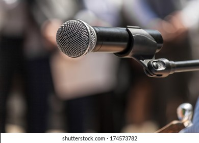 Microphone on the background blurred figures of people during a rally closeup