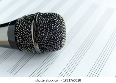 Microphone on a blank musical white sheet close up. Singing, writing music, karaoke online, creativity, vocals concept, symbol. Singing lessons