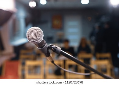 microphone on the holder, background auditorium outside focus and lights on the ceiling, musical apartment