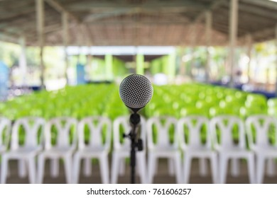 A microphone on microphone holder with line of green and white plastic chair background.