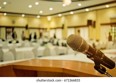 Microphone on podium with abstract blurred of conference hall or seminar room event background