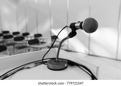Microphone on the podium in a seminar room where there are chairs for audiences. Close-up of the microphone in black and white.