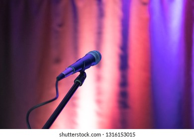 microphone on stage, background curtain illuminated
