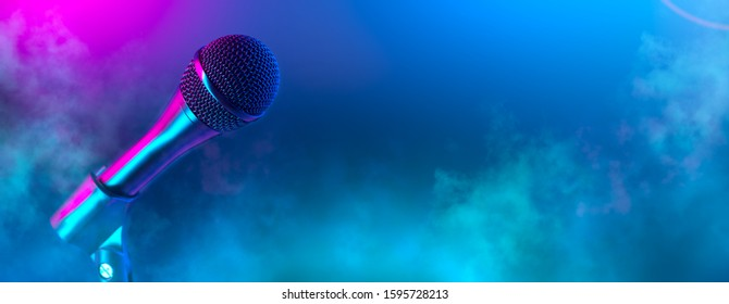 Microphone on stage close-up. Mic closeup. Karaoke, night club, bar. Music concert. Mike over colorful lights background. Song, music concept wide backdrop, border art design