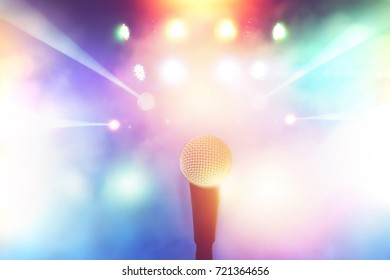 microphone on stage in concert hall with colorful light blurred background
