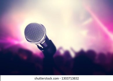 Microphone on stage, crowd of people in the club. Nightlife, entertainment. Concert and music industry.