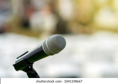 Microphone on the stage over the Abstract blurred photo of another music equipment on the stage background , Musical and presentation concept