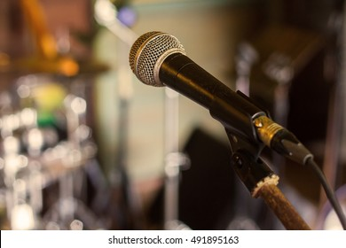 Microphone. A microphone on stage. A pub. Bar. Restaurant. Night show. Over music band blur background.