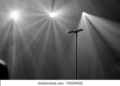 microphone on stage with spot light beams on the background