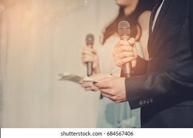 microphone on stage with two Presenters
