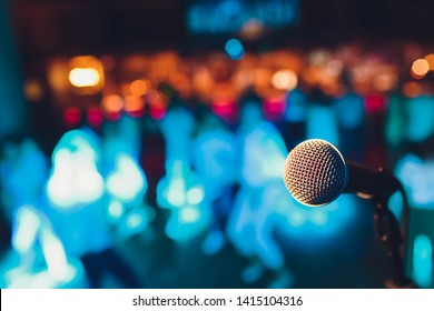 microphone on a stand up comedy stage with colorful bokeh , high contrast image.