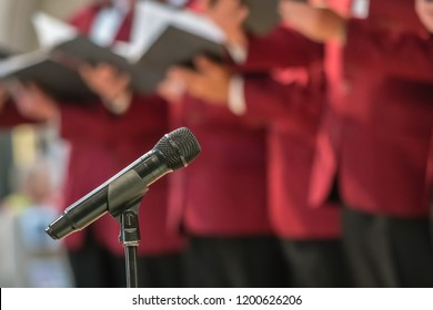 Microphone on a stand in front of mens choir members holding singing book while performing in a cathedral in Rochester, Kent, UK