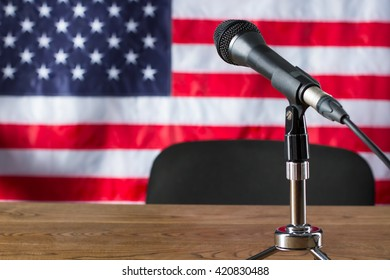 Microphone on USA flag background. Flag, microphone and chair. Workplace of news host. TV show about to begin.
