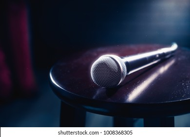 microphone on a wooden stool on a stand up comedy stage with reflectors ray, high contrast image