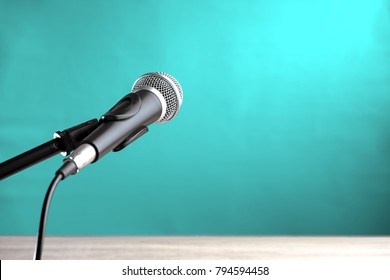Microphone on wooden table with turquoise wall background