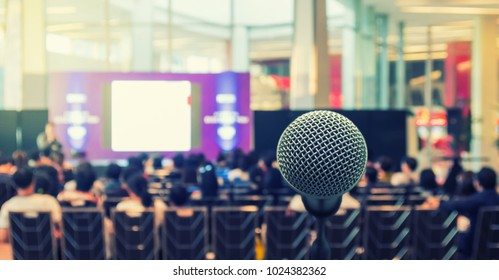 Microphone over the Abstract blurred photo of conference hall or seminar room with Speakers on the stage and attendee background, Business meeting concept