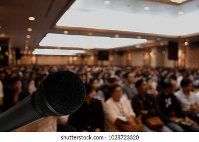 Microphone over the abstract blurred photo background. Abstract blurred photo of conference hall or seminar room with attendee background.  Business board meeting concept.