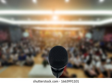 Microphone over the Abstract blurred photo of conference hall or seminar room with attendee background,Small Business training concept,Public speaking