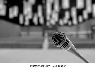 Microphone over the Abstract blurred photo of conference hall or seminar room background. Black and white tone.