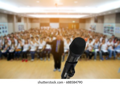 Microphone over the Abstract blurred photo of conference hall or seminar room with attendee background,group photographer training concept