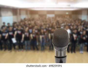 Microphone over the Abstract blurred photo of conference hall or seminar room with attendee background,Public Speaking concept.