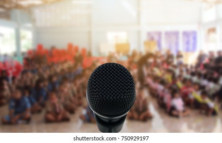 Microphone over the Abstract blurred photo of conference hall or seminar room with attendee background,Small Business training concept,Public speaking using as background and wallpaper.