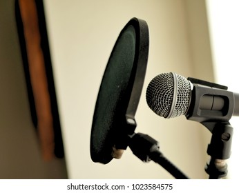 A microphone and pop filter set up in recording studio vocal booth.