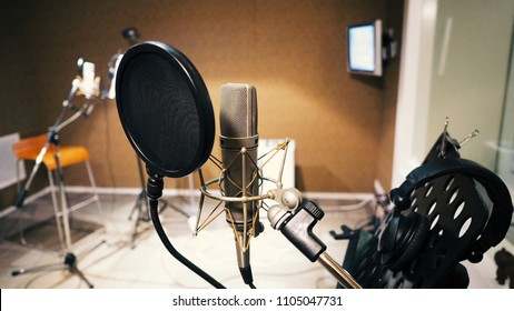 Microphone with pop filter and shock mount anti-vibration and note stand and tripod in music score studio production
