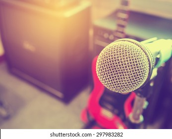 Microphone in a recording studio or concert hall with amplifier in out of focus background. : Vintage style and filtered process.