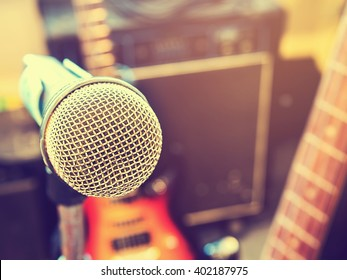 Microphone in a recording studio or concert hall with electric guitar in out of focus background. : Vintage style and filtered process.