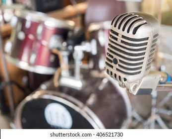 Microphone in a recording studio or concert hall with drum in out of focus background.
