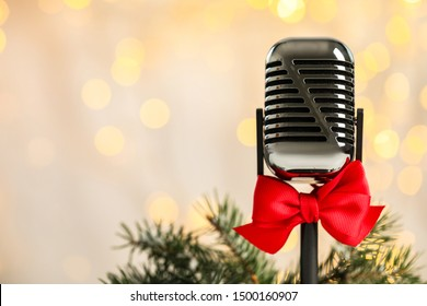 Microphone with red bow and fir branches against blurred lights, space for text. Christmas music