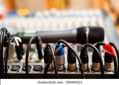 Microphone resting on music mixer