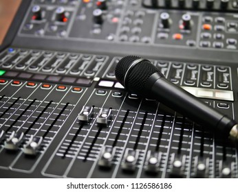 microphone rests on an audio mixer controller in the control room, Sound mixer control for live music and studio equipment, Quality audio system for professionals, music equipment concept