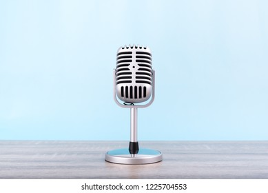 Microphone retro Put on wooden table isolated on blue background.