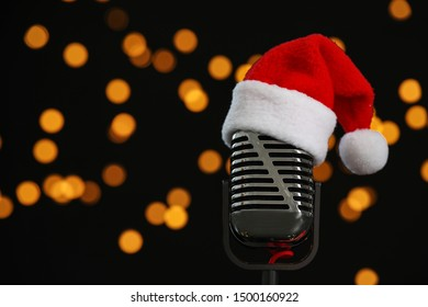 Microphone with Santa hat against blurred lights, space for text. Christmas music