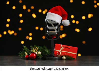 Microphone with Santa hat and decorations on grey stone table against blurred lights. Christmas music