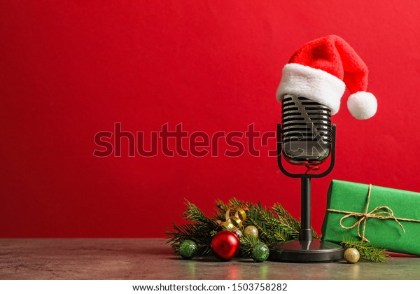 Microphone with Santa hat and decorations on grey table against red background, space for text. Christmas music