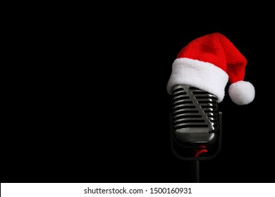Microphone with Santa hat on black background, space for text. Christmas music