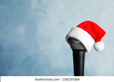 Microphone with Santa hat on color background. Christmas music concept