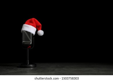 Microphone with Santa hat on grey stone table against black background, space for text. Christmas music