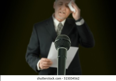 Microphone in sharp focus with a nervous sweaty public speaker or politician blurred in the background preparing to make a speech as he wipes his brow